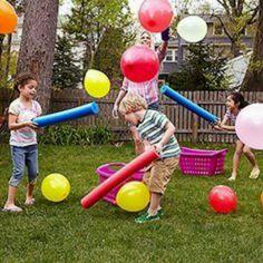 children hitting balloons with pool foam